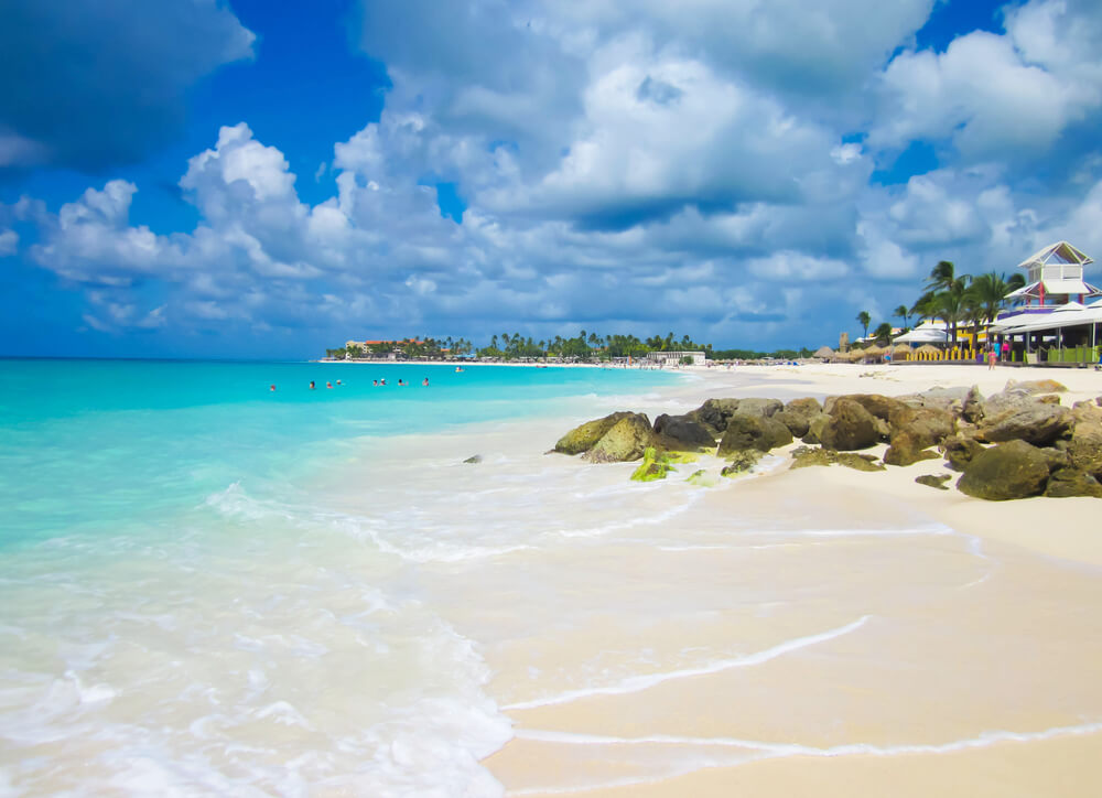 A photo of a beautiful beach in Aruba. It shows a white sandy beach with calm light blue waters lapping against it. On the right hand side of the image is a small resort. The sky is slightly cloudy