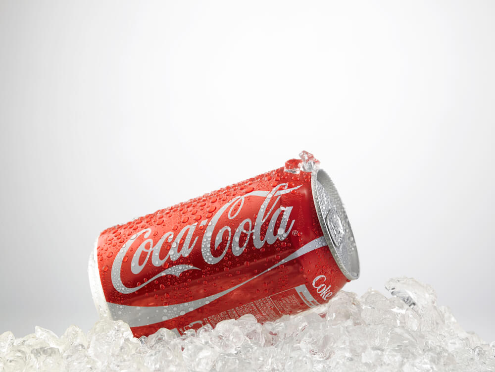 A photo of a can of an unopened coke laying on a bed of ice chips. The can is bright red and features the words Coca Cola
