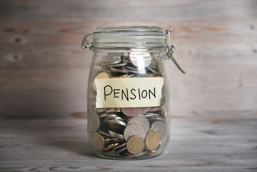 A photo of a glass jar contains dozens of coins. On the jar is a hand written label with the word pension