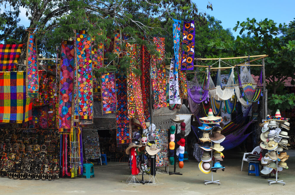 A photo of a outdoor shopping stall in Tulum, Mexico. It shows large tables and racks with the colorful clothing and hats