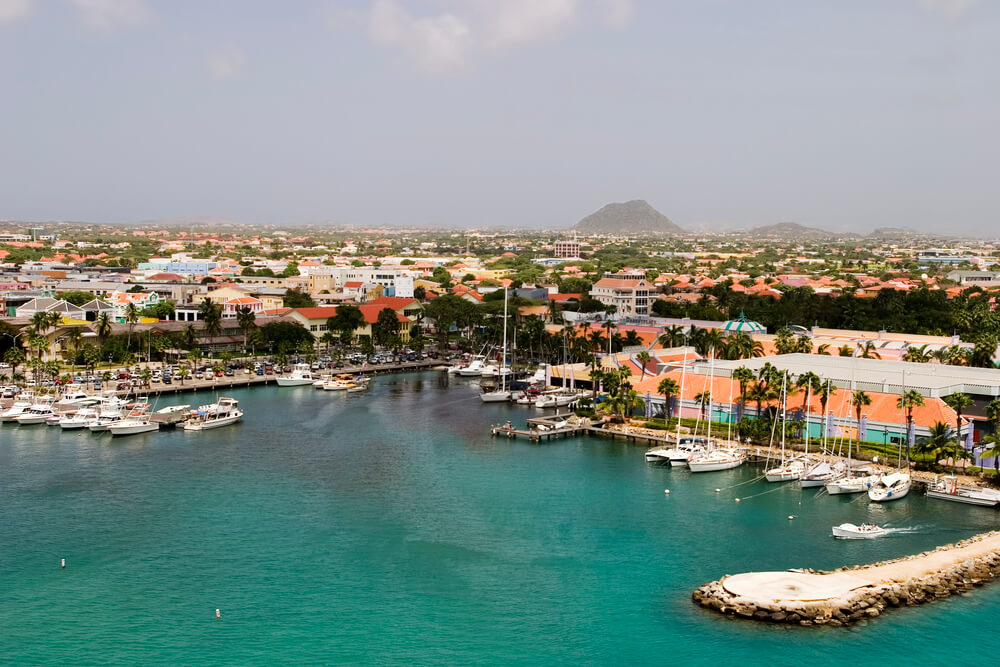 A photo of a tropical harbour in Aruba. It shows a large harbour with several yachts. Surrounding the harbour are dozens of colourful homes
