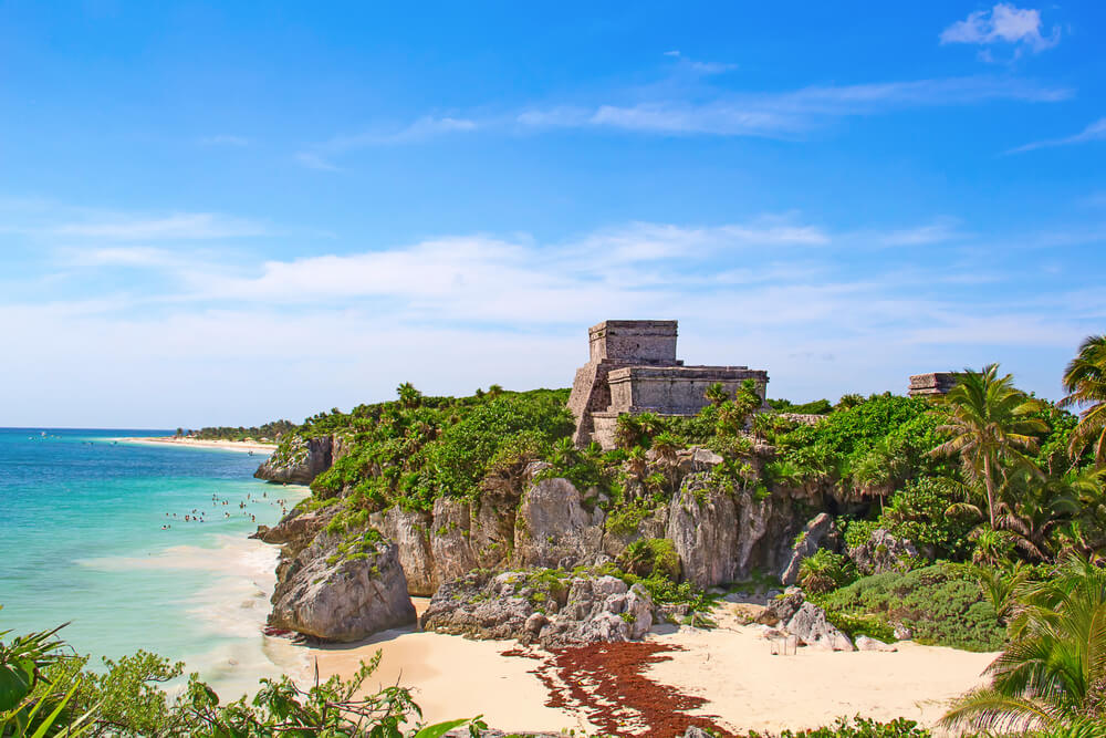 A photo of an ancient Mayan ruin located on a hill next to a beach in Tulum, Mexico. It shows a huge stone ruin overlooking the water and surrounded by palm trees