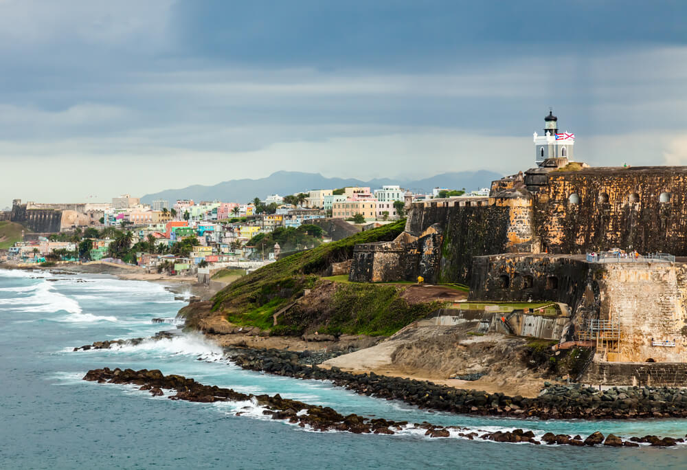 A photograph of El Morro Fortress, San Juan in Puerto Rico. It shows a huge brick fortress on a cliff face overlooking the ocean, In the distance is the town of San Juan