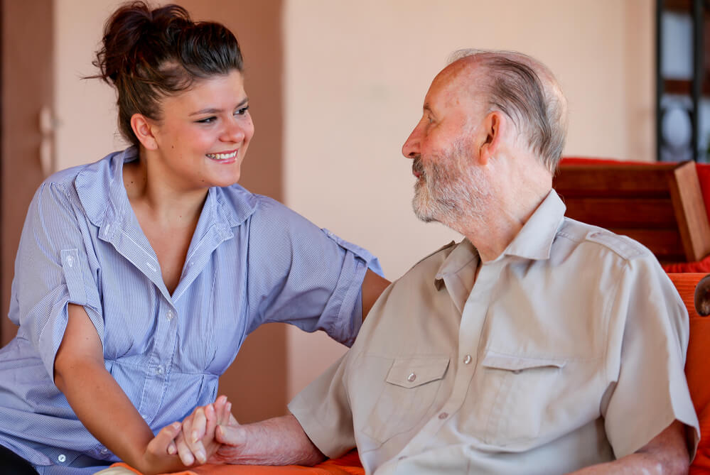 An elderly male is sitting in a chair as he chats with a assisted living nurse