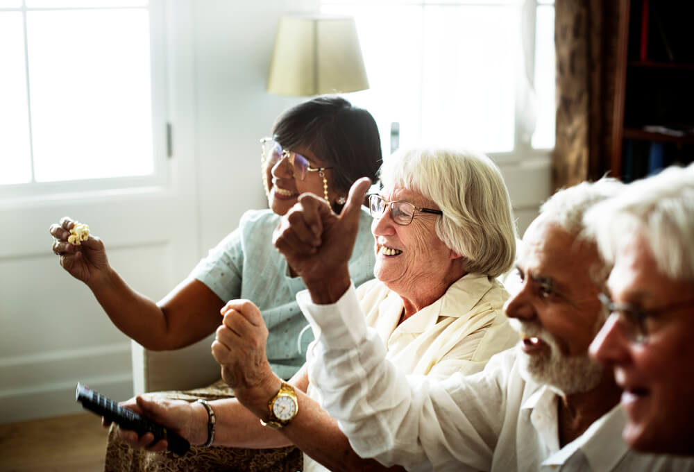 An image of a group of elderly people siting together as they watch television. They all look very happy and are smiling