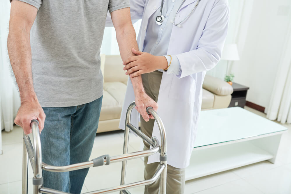 An image of an elderly man at home walking with help of doctor using a walker
