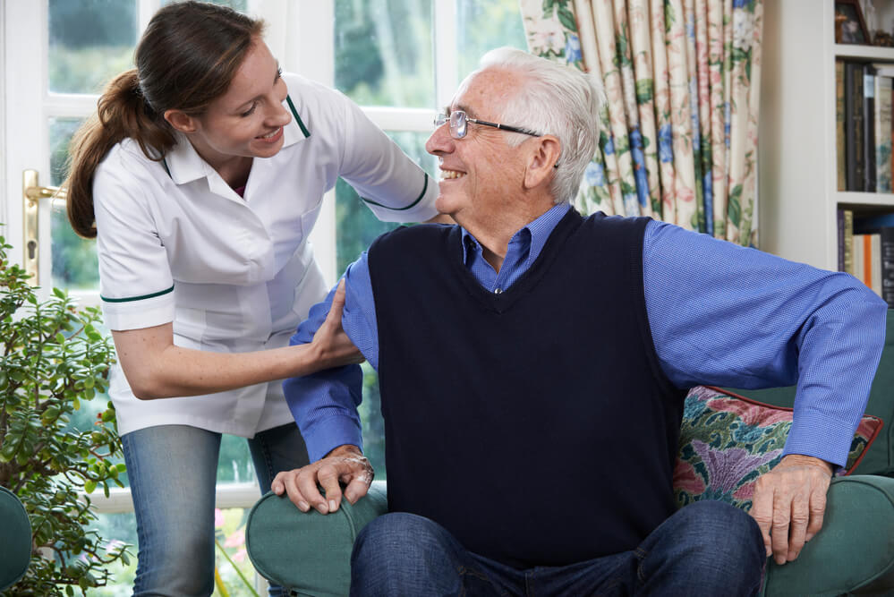 An image of an elderly man with white hair seated in a chair in an assisted living home. He is looking up at female carer