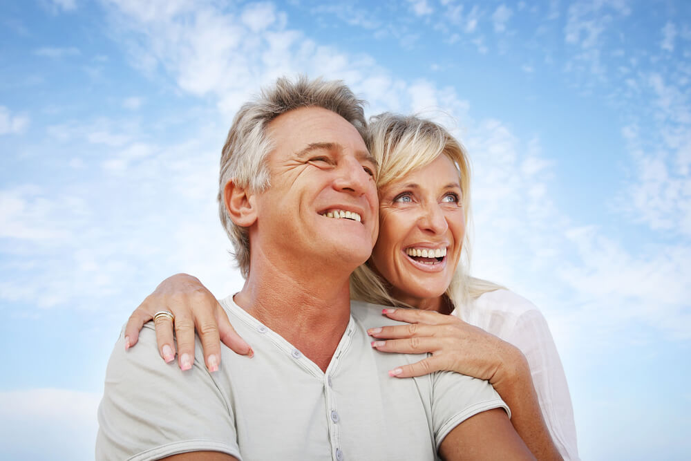 An image of an older over 55 couple who are siling and looking towards the sky