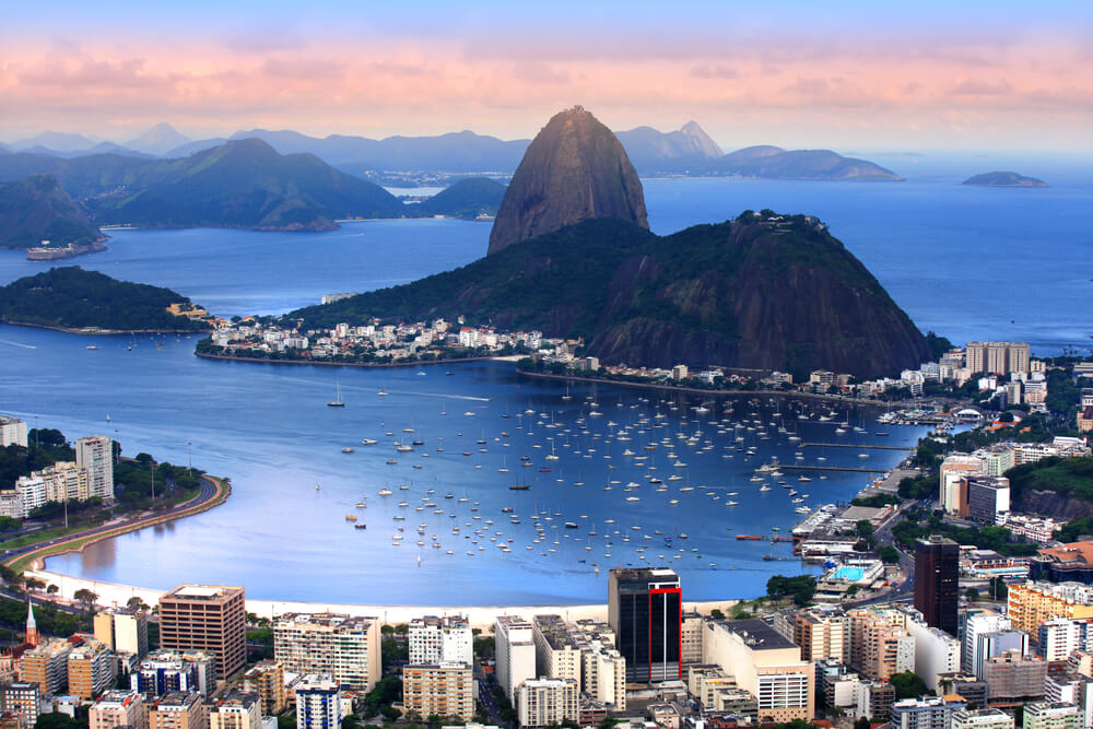 An image of the bay in Rio De Janeiro, Brazil. It shows a large bay surrounded by hundreds of buildings. An archipelago is situated in the bay and there are dozens of boats