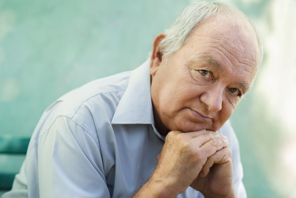An older male is sitting down and looking at the camera with a concerned look on his face