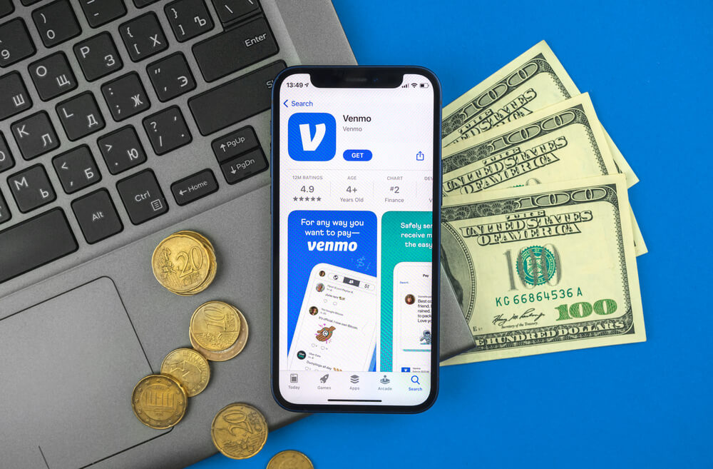 A photo of a phone showing the Venmo app. The photo also shows some coins, paper currency, and a laptop computer