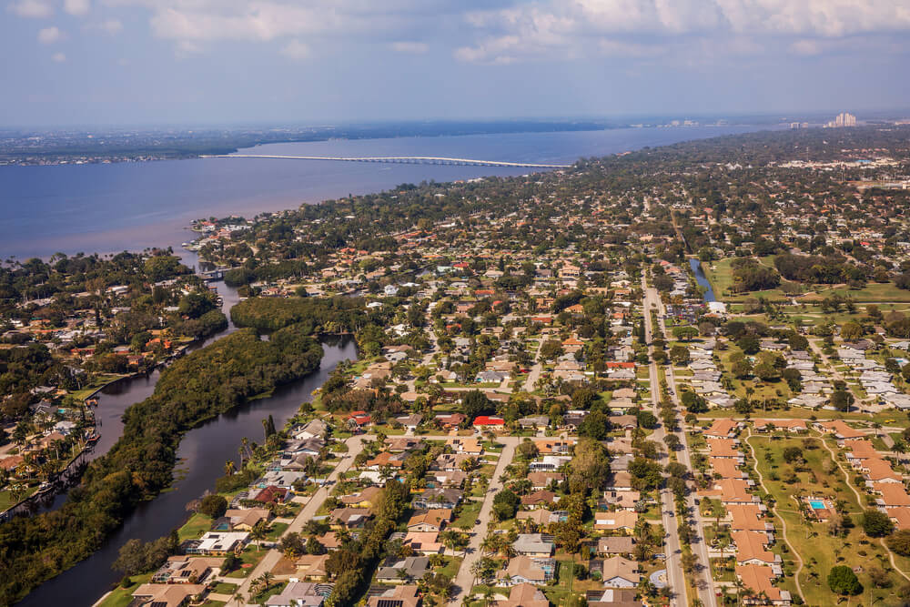 An aerial photo of metropolis Fort Myers and Cape Coral in south Florida. It shows dozens of houses adjacent to a water which runs to the sea