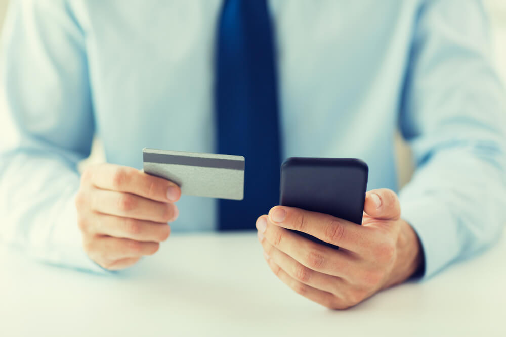 Man in a blue tie is holding a credit card in one hand and smart phone in other hand
