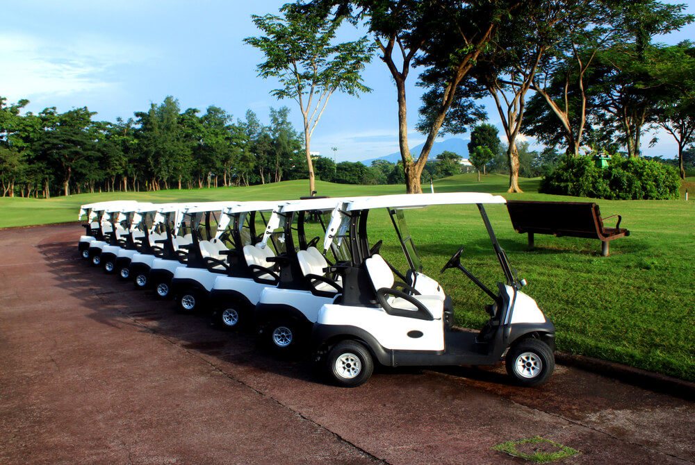 10 golf carts are lined up next to each other at a golf course