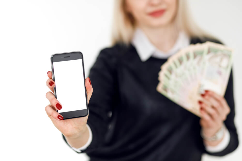 A young lady is holding a smartphone in one hand and cash bills in the other hand