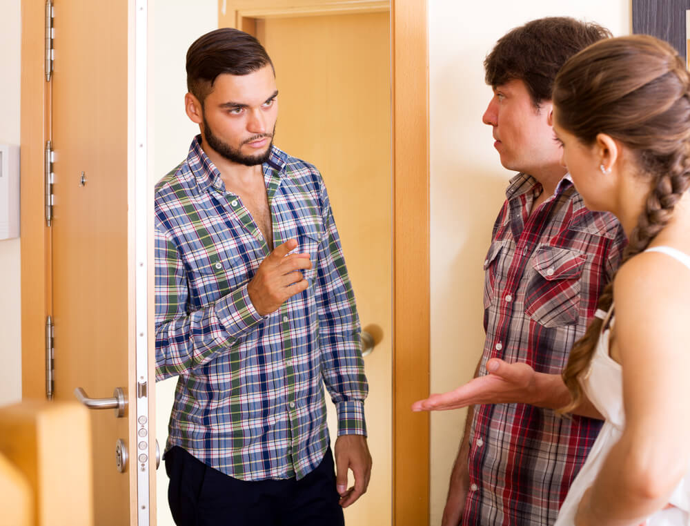 A man is at the door, appears to be scolding a younger couple in the room