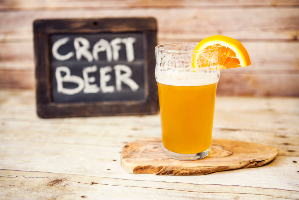 """A picture of a glass of beer sitting on a wood coaster with a half orange slice hanging on glass. In the background is a sign titled """"Craft Beer."""""""