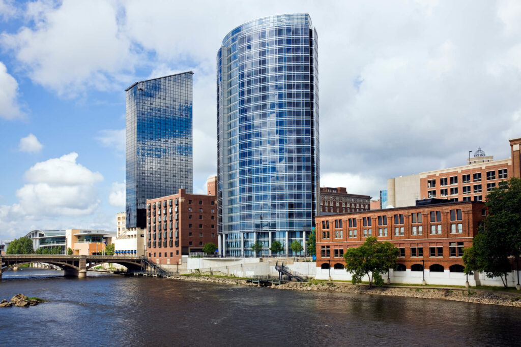 Grand Rapids skyline with the Grand River flowing in front with bridges going over the river. Brown brick buildings and glass high rises.