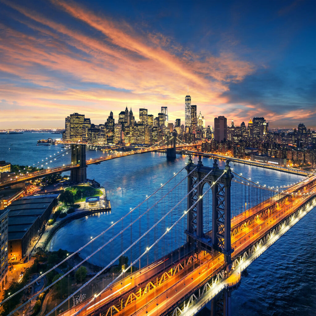 An aerial view of Manhattan. Lots of city lights and bridges. City skyline at dusk.