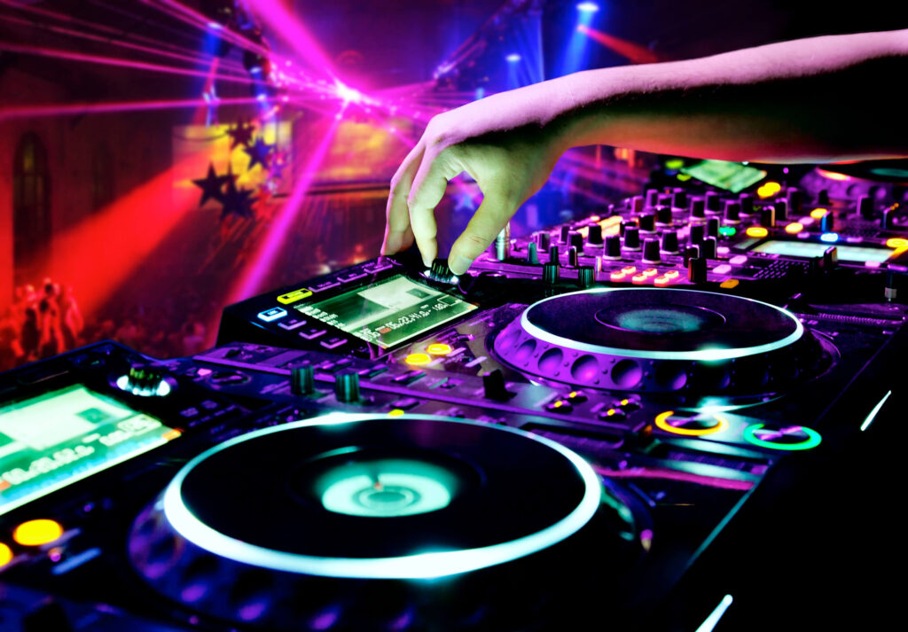 A picture of a hand controlling a DJ turn table. Lots of pink and red club lights as well as people dancing.