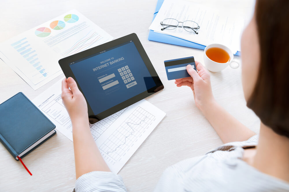 """A picture of a woman holding a credit card and a tablet computer. The tablet reads """"internet banking."""" On the table are papers with graphs and charts as well as tea and glasses."""