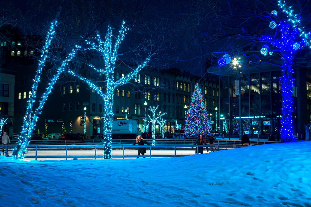 A picture of Rosa Parks downtown Grand Rapids in the winter. Lots of Christmas lights on the trees and snow covered ground. People skating on the ice rink.