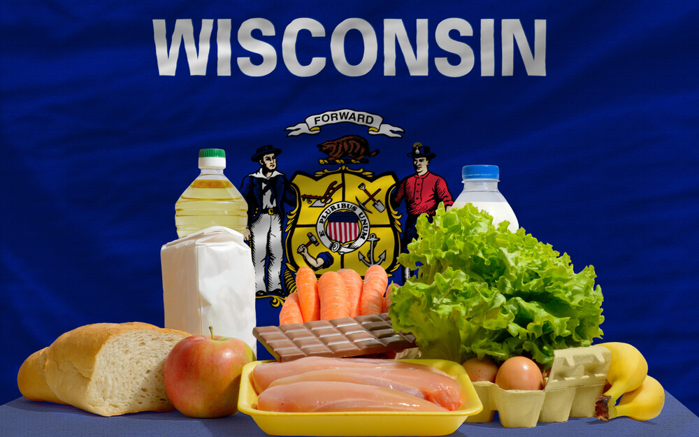 A staged photo showing the Wisconsin flag as the background and various milk and farm products in the foreground.
