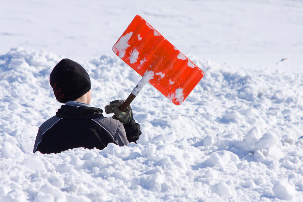 A boy stands in snow up to his shoulders, with an orange snow shovel in his hands