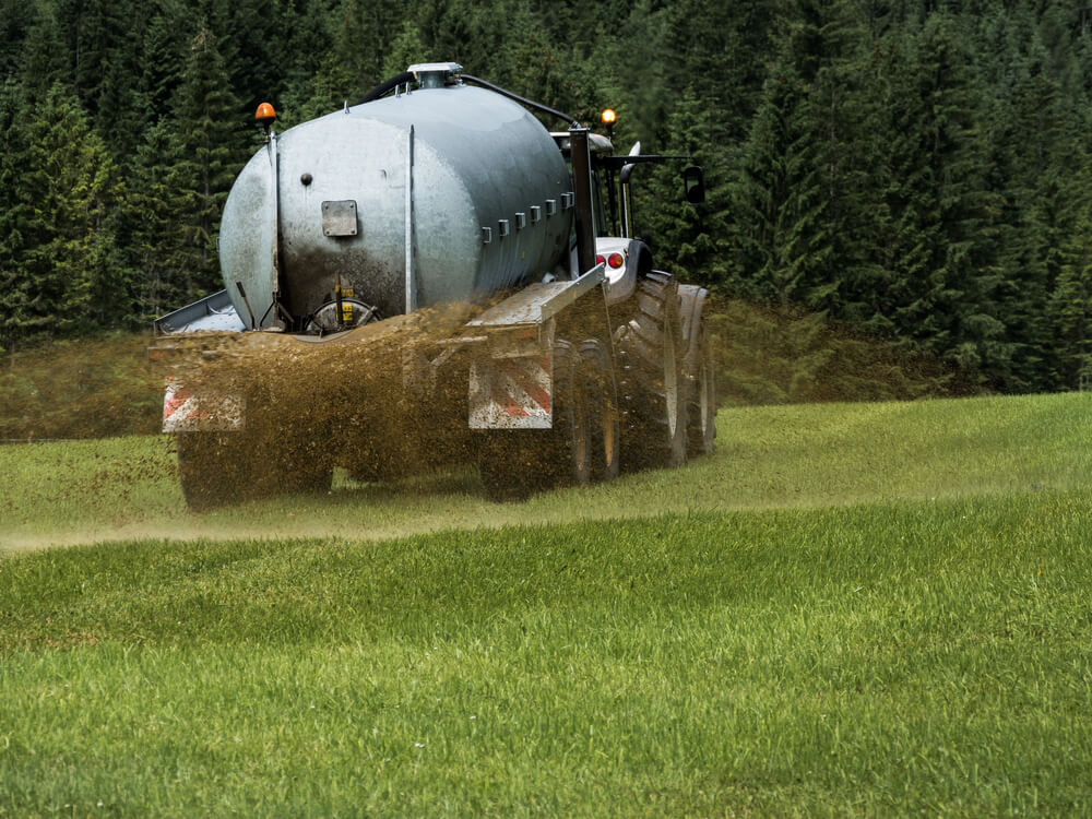 A tanker truck spreads manure on a green field of grass.
