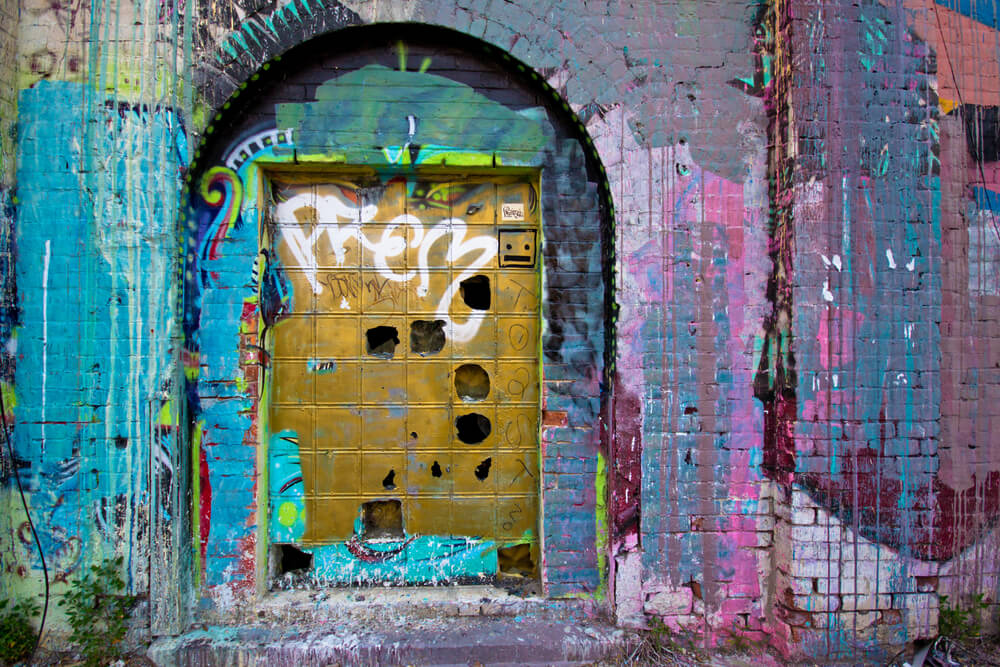 A picture of a degrading building, covered in colorful graffiti