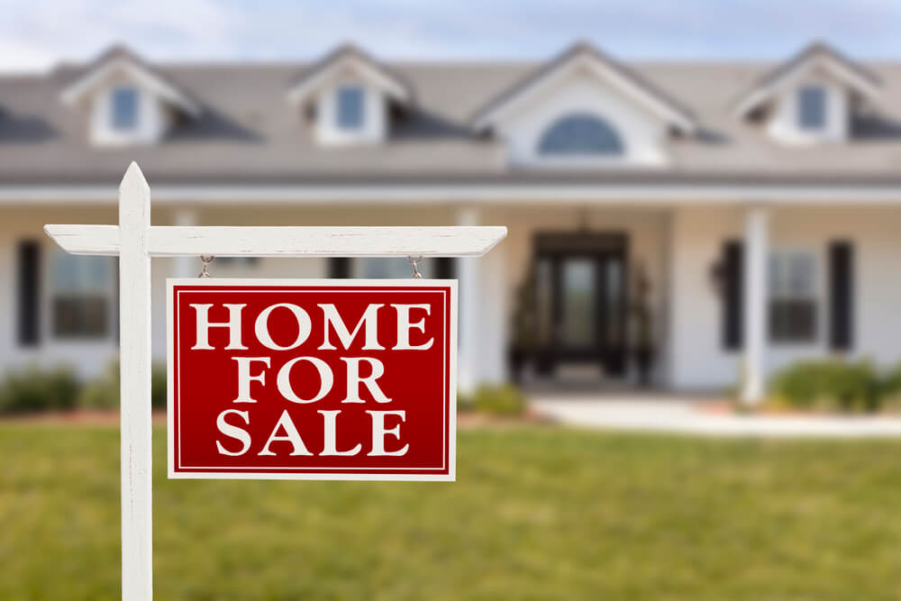 """A red sign with large white text that says """"Home For Sale"""". A blurry house sits in the background."""