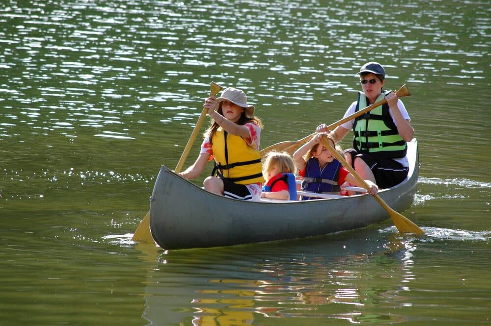 A woman and three kids paddle a canoe across a calm lake