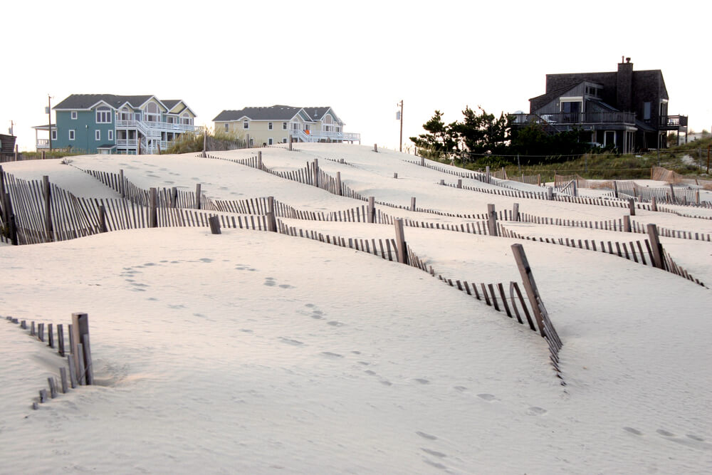 A photo of 3 beach homes in the back, and sand dunes in the front