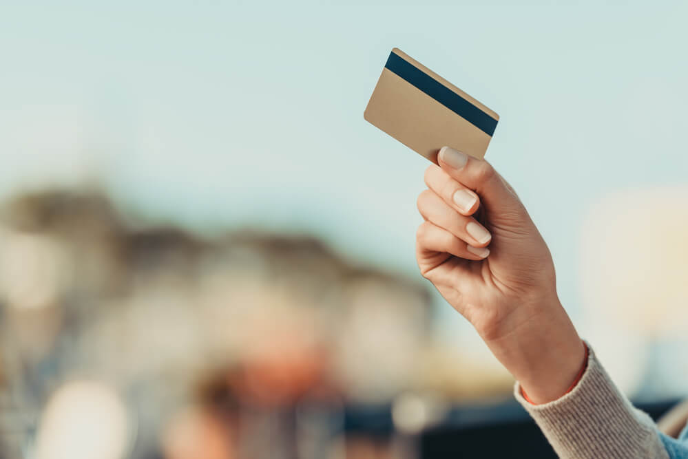 A woman's hand is see holding a gold debit card
