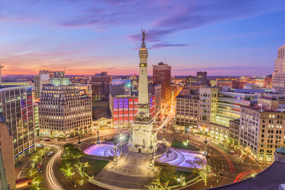 An aerial photo of downtown Indy. A traffic circle surrounds a tall statue. Tall buildings can be seen on all sides.