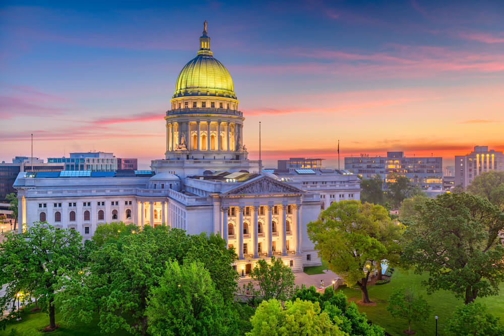 A photo of the Madison capitol building, which closely resembles the US Capitol building. Green trees are in the foreground, a few buildings in the background, and the sunset sky is blue and pink.