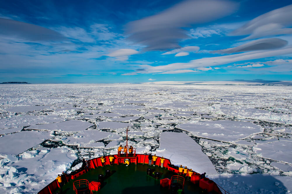 A photo of an ice-breaker ship, traveling in the waters, surrounded by ice