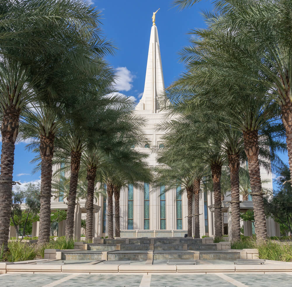 Photo of a famous church in Gilbert. A line of palm trees leads to a white temple