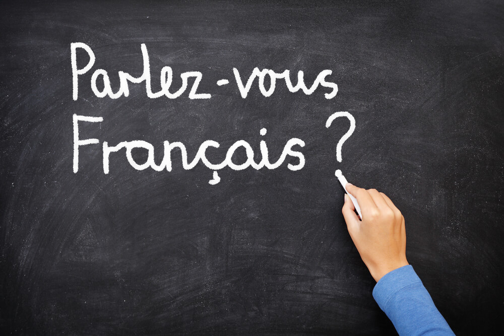 """A person is using white chalk on a blackboard to write """"Parlez-vous Francais?"""""""