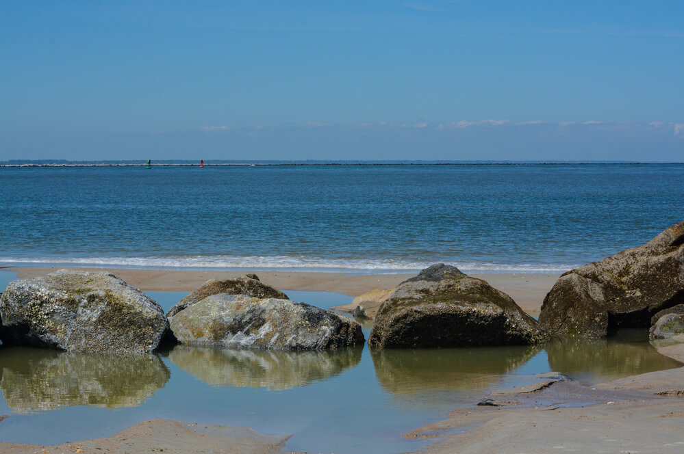 A photo of a beach. Sand and large rocks in the front, blue water in the back