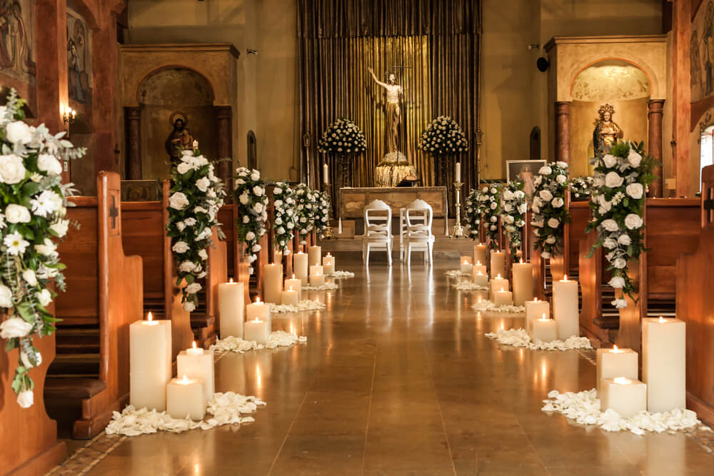A photo of a very ordained catholic church full of really big candles and lots of white flowers