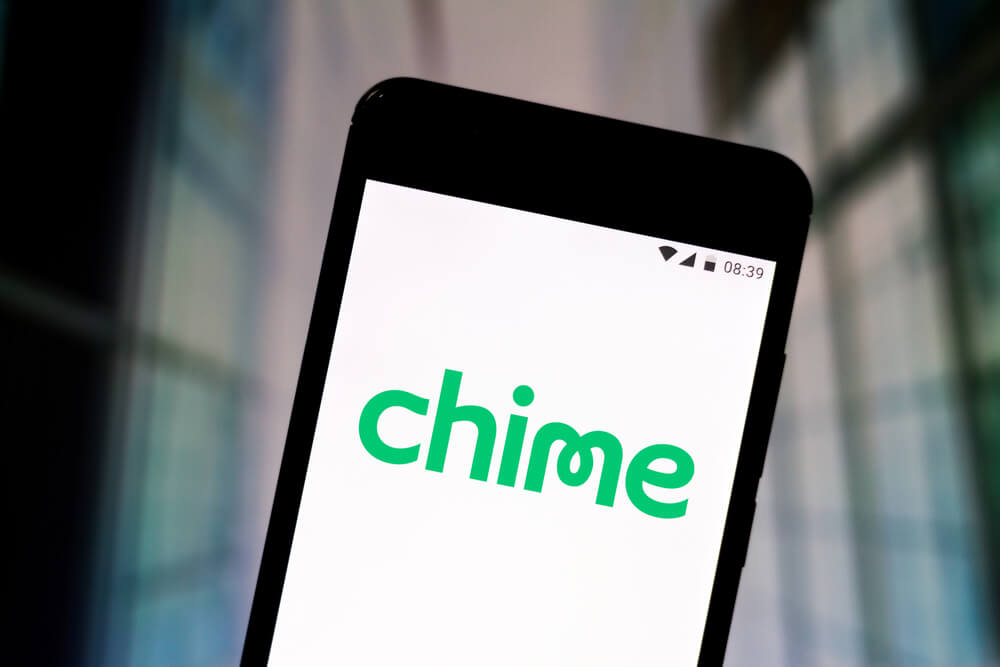 """A close-up view of a black cell phone. On the screen it simply says """"Chime"""" in green text"""