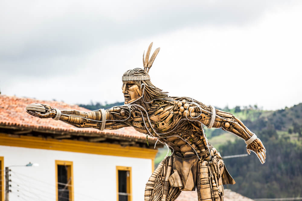 A gold color statute of an indigenous man, supposedly a god, throwing a tejo disc