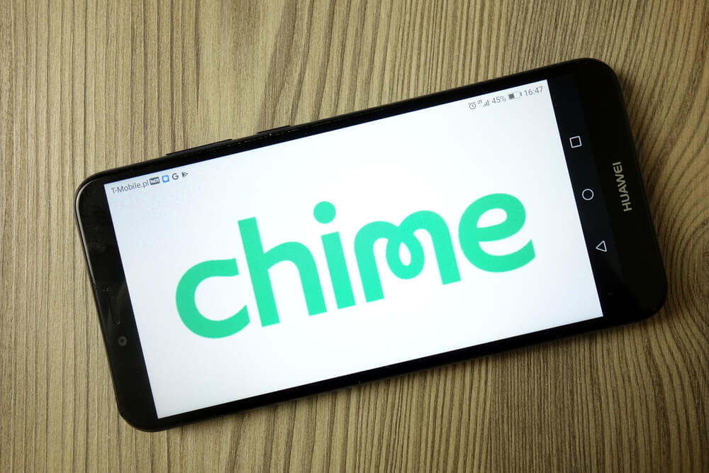 """A cell phone is laying on a wooden table. One the screen is the word """"Chime"""" written in a green font."""