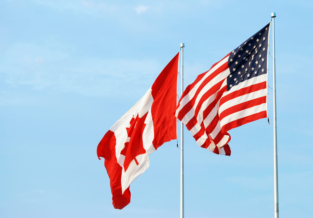 Photo of the Canadian and US flags waving in the breeze