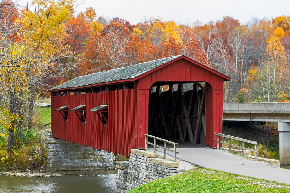 A photo of a red covered bridge. The trees in the background are showing autumn foliage