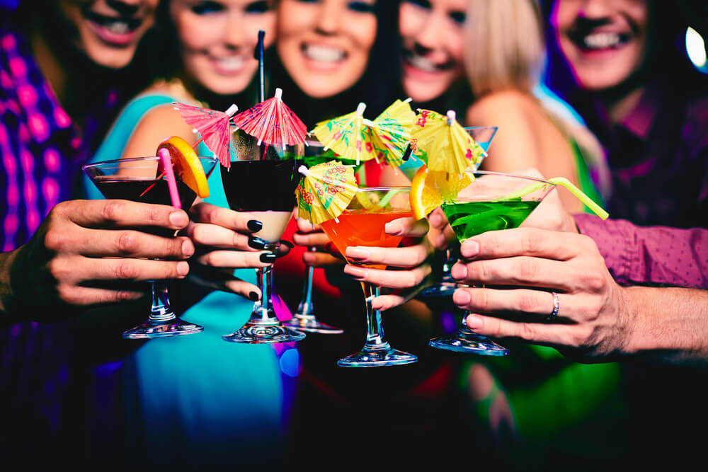 Five people are lined up, holding colorful cocktail glasses in front of them.
