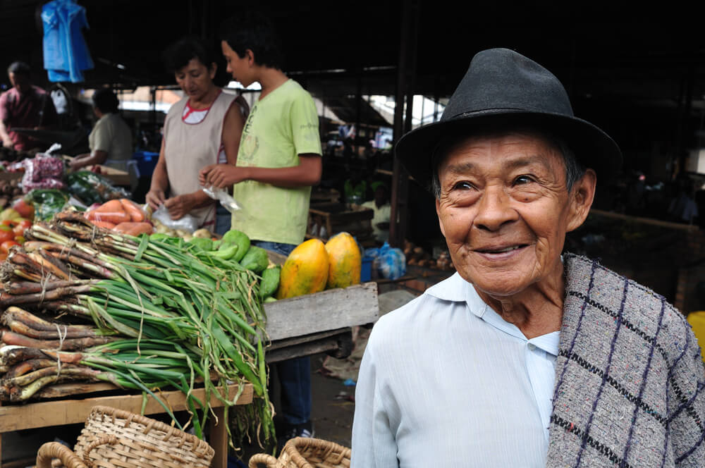 An older man wearing a black fedora hat stands in a market, where we can see bunches of vegetables
