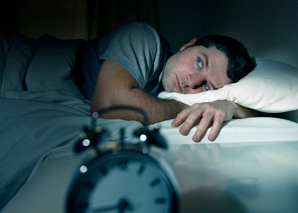 A man lies in bed, staring into the distance. A blurry alarm clock appears in the foreground.