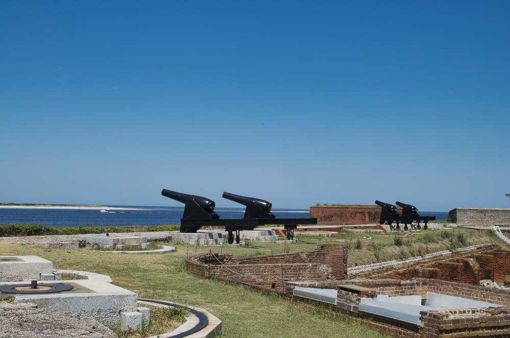 A photo of the ruins of Fort Clinch. Brick and stone foundations can be seen on the green grass. There are 4 replica cannons pointing out to the blue water.